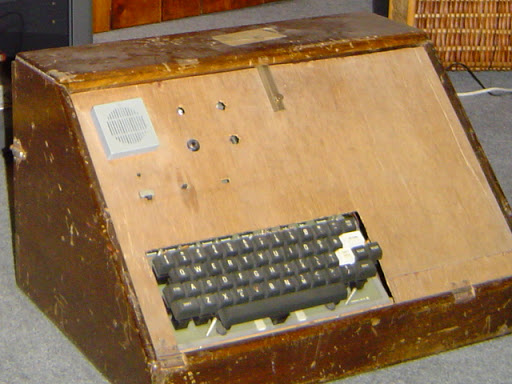 Large and scruffy wooden box with speaker and keyboard visible