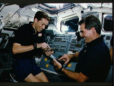 two space shuttle crewmembers on with an HP-48 scientific calculator
