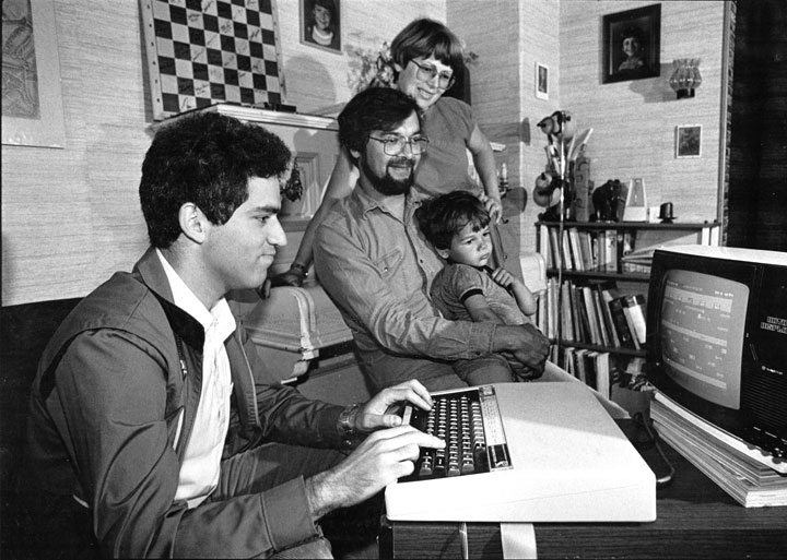 Kasparov plays a video game as toddler looks on
