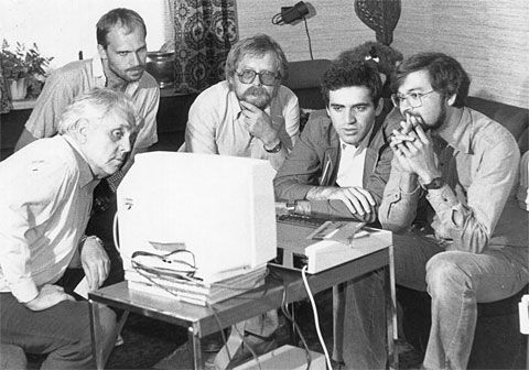 Kasparov and journalists in deep thought in front of a BBC Micro