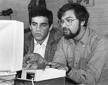 Kasparov and another man in discussion over a BBC Micro